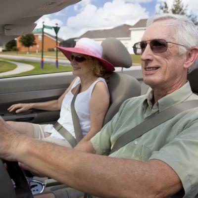 Senioren am Steuer mit Sonnenbrille.