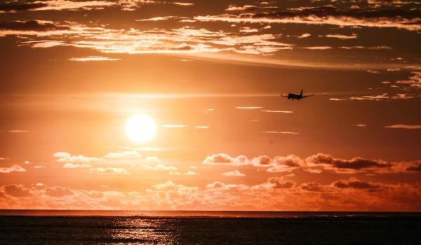 Sonnenuntergang über dem Meer, ein Flugzeug ist am Himmel sichtbar.