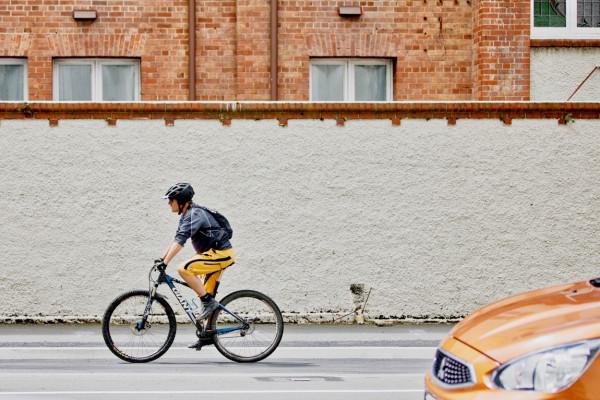 Ein Fahrradfahrer fährt auf der Straße neben einer weißen Mauer. Im Vordergrund rechts ist die Motorhaube eines Autos zu sehen.