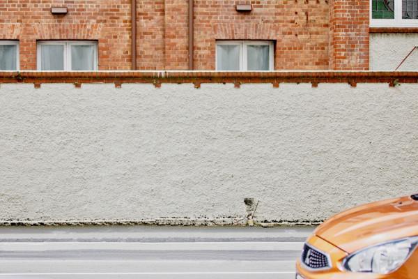 Straße an weißer Mauer, vorne rechts ist die Motorhaube eine Autos zu sehen.