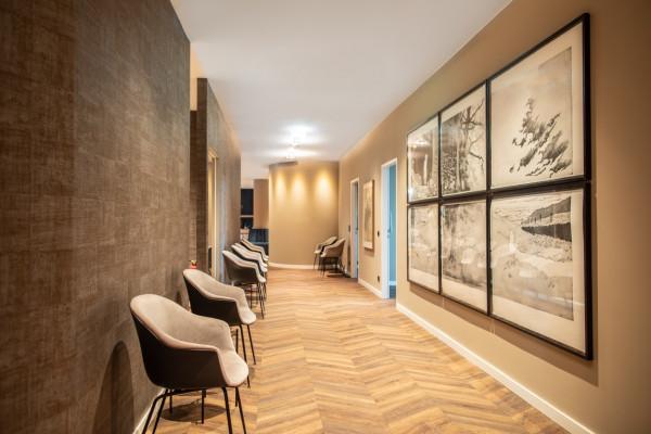 Blick in den Gang einer Arztpraxis. Links sind gemütliche Stühle, gegenüber hängen Illustrationen an der Wand.