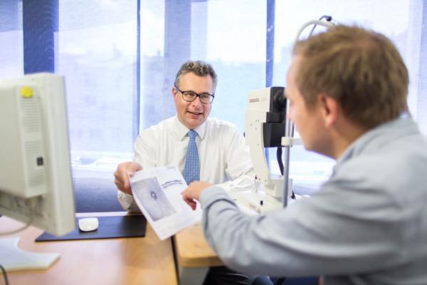 Augenarzt Dr. Kristian Keitel erklärt seinem Patienten einen OCT-Befund.