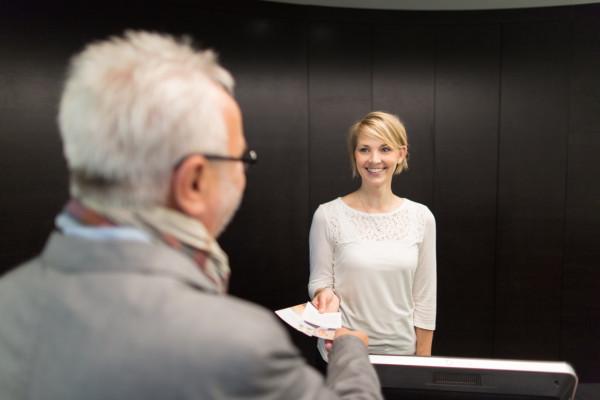 Eine Mitarbeiterin am Empfang übergibt dem Patienten seine Unterlagen.